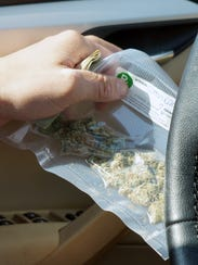Logan Martyn-Fisher holds a vacuum-sealed bag of marijuana