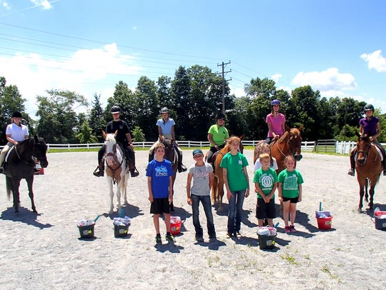 4-H Horse Club members and family members standing,