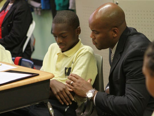 Dr. Lamont Browne, head of school/principal, of EastSide Charter School gives support to Sy'Mere Thomas, 11, a fifth grader, while stopping in his class.