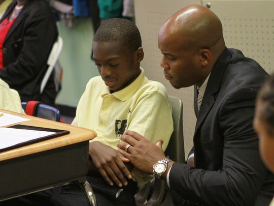 EastSide Charter School's school leader, Lamont Browne, gives support to Sy'Mere Thomas, 11, a fifth-grader, while stopping in his class in September. Browne will now also take charge of Family Foundations Academy charter school.