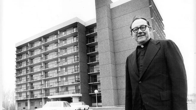 On April 8, 1980, the Rev. Gerald Dunn stands near Dunn Tower II, part of a project he initiated to provide housing for seniors in Gates.