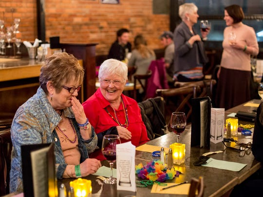 "Helen Weston, of Port Huron, and Janet Hanson, of Fort Gratiot, laugh together as they drink wine during a First Presbyterian Church ""Fermenting Faith"" event Tuesday, Feb. 28, 2017 at The Vintage Tavern in Port Huron."