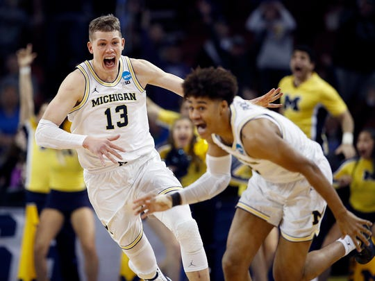 Michigan guard Jordan Poole (2) is chased by forward Moritz Wagner (13) after Poole made a 3-point basket at the buzzer to win an NCAA men's college basketball tournament second-round game against Houston on Saturday, March 17, 2018, in Wichita, Kan. Michigan won 64-63. (AP Photo/Charlie Riedel)