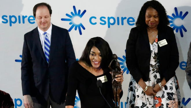 Mississippi State's Victoria Vivians delivers comments as she holds onto her C Spire Gillom Trophy, Monday, March 5, 2018, at the Mississippi Sports Hall of Fame in Jackson, Miss., moments after being awarded the trophy given to the state's top women's college basketball player. C Spire CEO Hu Meena, whose company is the title sponsor of the award, left, and Peggie Gillom-Granderson, right, for whom the award is named, listen from behind.