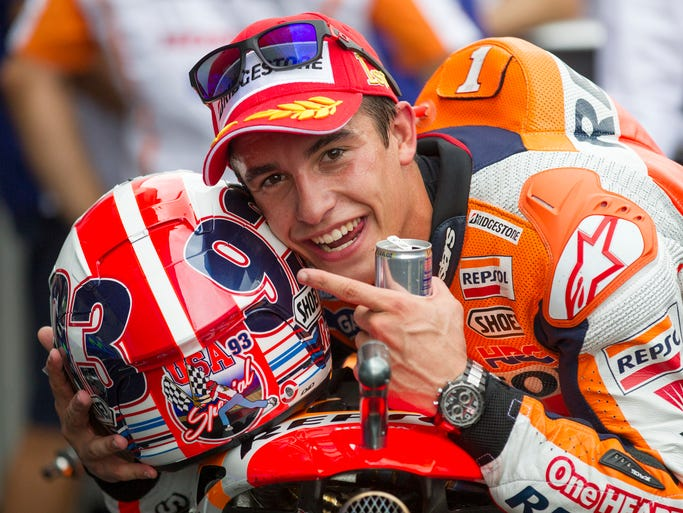 Marc Marquez poses for photographers after his winning Moto GP race, Indianapolis, Sunday, August 10, 2014.