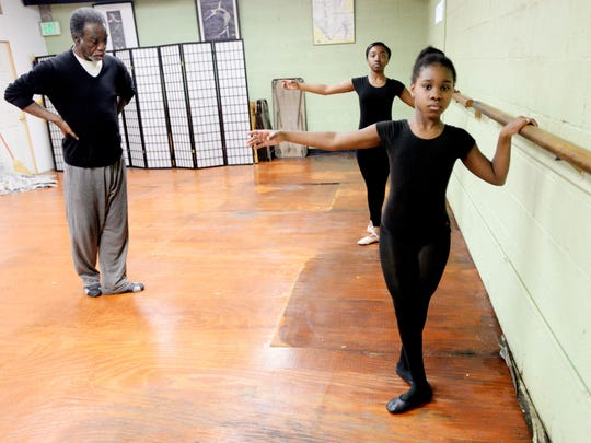 Luther Cox, Jr. teaches Cayla Oliver and Terra Williams, right, during a dance class at the Inter City Row Modern Dance Company.