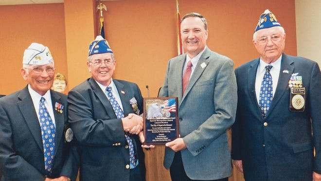Rogersville Mayor Jack Cole accepts a plaque designating Rogersville a Purple Heart City from veterans, from left, Jimmy Young, Everett Kelly and John Dismer of the Military Order of the Purple Heart.