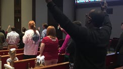Willie Cox of Jackson raises his hands in worship at