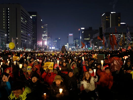 FILE - In this Jan. 21, 2017, file photo, protesters stage a candlelight vigil calling for impeached President Park Geun-hye to step down in Seoul, South Korea. The Pyeongchang Olympics have been drawn into the country's biggest political scandal in decades. Prosecutors say Park and her longtime friend Choi Soon-sil plotted to pressure businesses to donate tens of millions of dollars to two nonprofit foundations controlled by Choi, one of them sports-related. (AP Photo/Ahn Young-joon, File)