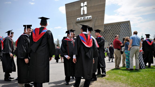 St. John's University graduates talk with family and friends before the start of their commencement ceremony Sunday in the St. John's Abbey and University Church. Former Minnesota Chief Justice Kathleen Blatz was the guest speaker.