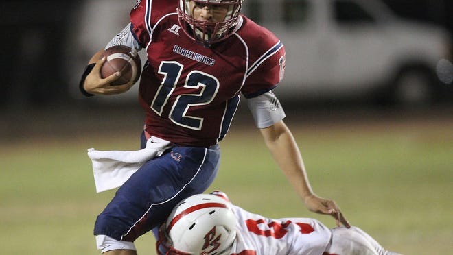 La Quinta quarterback Michael Avina is tackled by Palm Springs' Franklin Miller druing a back-and-forth classic Friday. The Blackhawks won 34-29.