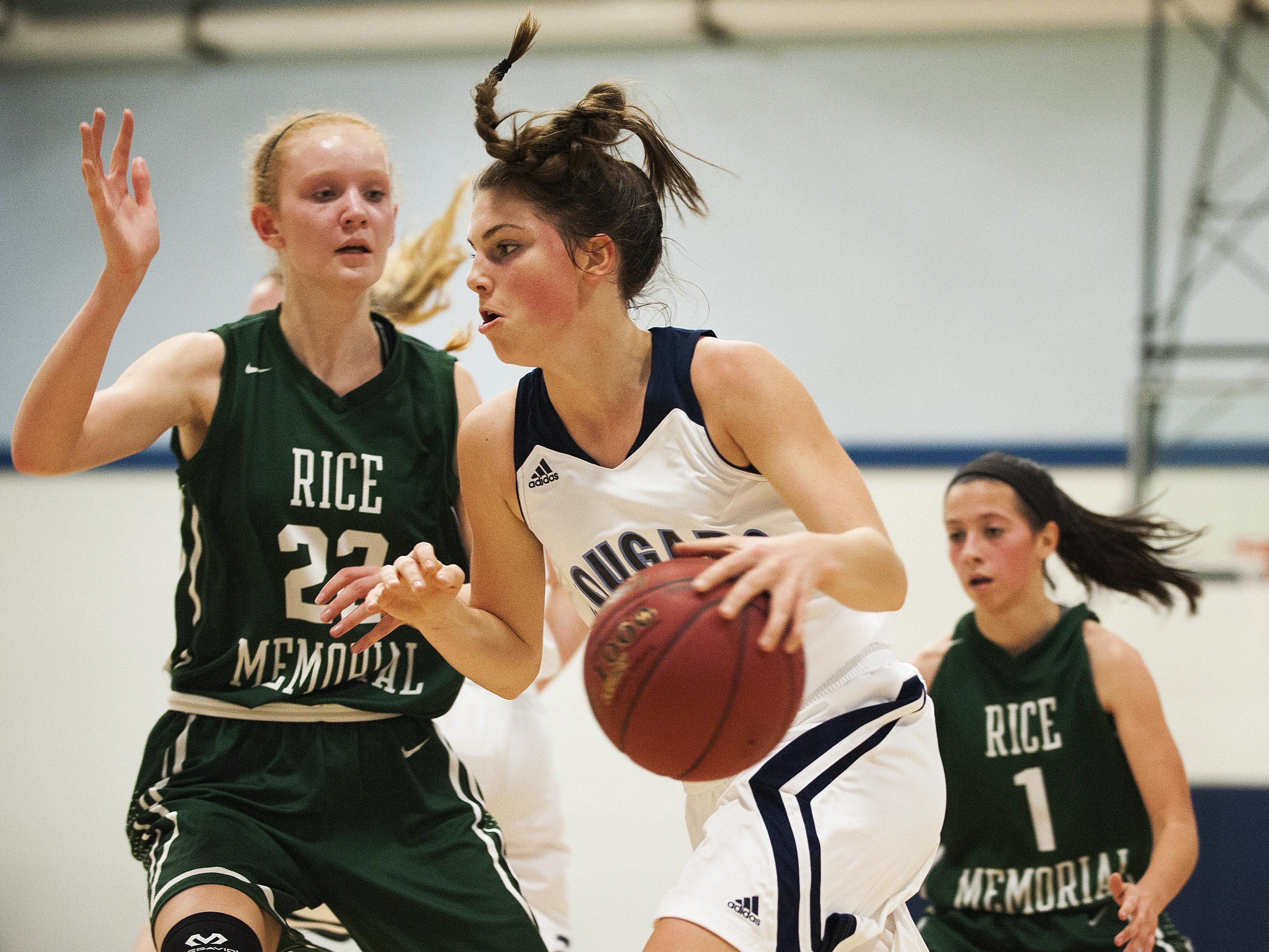 Mount Mansfield forward Perry Willett (5) drives to the hoop past Rice forward Lizzy Lyman (22) during the girls basketball game between the Rice Green knights and the Mount Mansfield Cougars at MMU High School on Friday night December 4, 2015 in Jericho.