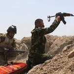 Iraqi soldiers fire towards Islamic State as they attempt to re-take Ramadi, Iraq.