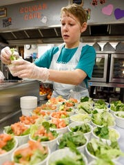 Jonathon Becker, 12, puts lettuce and tomatoes in individual