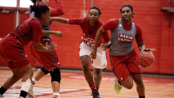 UL senior guard Jaylyn Gordon, middle, works on her defense while chasing freshman ball handler Jasmine Thomas during a Ragin' Cajun women's practice.