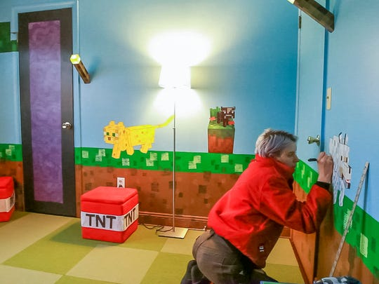 Emily Schaffner of Ithaca, puts the finished touches on Colin Hayward Toland's Minecraft themed bedroom Saturday afternoon.