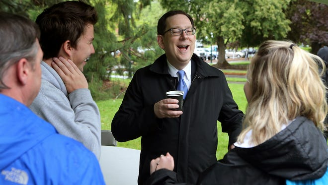 Incoming University of Oregon President Michael Schill, center, laughs and chats with UO students, staff and faculty at a small gathering outside Johnson Hall on campus Tuesday, May 12, 2015 in Eugene, Ore. The University of Oregon's incoming president is spending this week touring the campus, meeting with faculty and talking with students in preparation for his July 1 start date. (Paul Carter/The Register-Guard via AP)