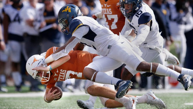 Texas quarterback Shane Buechele is taken down to end a run in the second half against West Virginia on Saturday in Austin.
