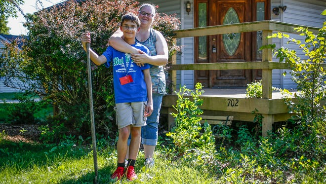 "Laura Warrick and her son, Jamie Baker, 12, pose for a photo in front of their new home on Wednesday, August 9, 2017. ""We're just waiting for the contractor to be done so we can move in,"" said Warrick. ""Coming in and being able to say this is my house and put paint on the wall was really exciting."""