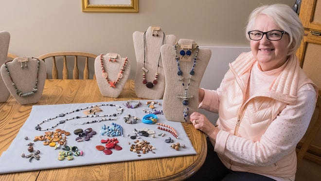 In this Friday, Dec. 15, 2017 photo, Paulette Bertrand, a retired graphic designer, displays some of her handmade jewelry at her home in Mankato, Minn. She makes beaded necklaces, earrings and bracelets out of fair trade certified beads from around the world. (Jackson Forderer/The Free Press via AP)