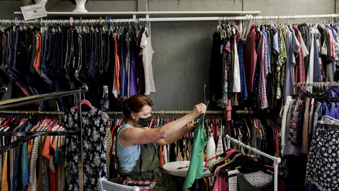 Manager Janet Hollifield looks through clothing items at Austin Pet's Alive Thrift store on Oltorf Street in Austin. Texas retailers reported a surge in sales in September, according to the Federal Reserve of Dallas.