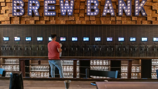 James Lucatero, an employee at Brew Bank, cleans off the taps Tuesday afternoon.