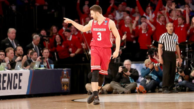 After hitting a game-tying three-pointer with 2.5 seconds left in regulation against Florida, Wisconsin guard Zak Showalter points in the direction of Packers quarterback Aaron Rodgers, who was in attendance at Madison Square Garden.