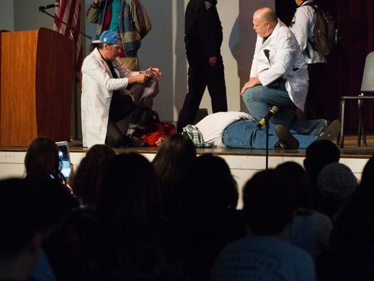 James Sassak, left, acting as a medic along with Ernest