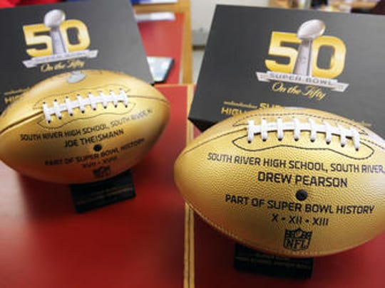 South River High School alums Joe Theismann and Drew Pearson, who each won a Super Bowl, have their commemorative championship golden footballs on display at their alma mater.