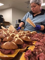 Employees of North Carolina-based MG Foods Inc. prepare sandwiches for distribution to the company's clients. MG Foods is considering expanding into Melbourne, creating 95 jobs over the next three years.