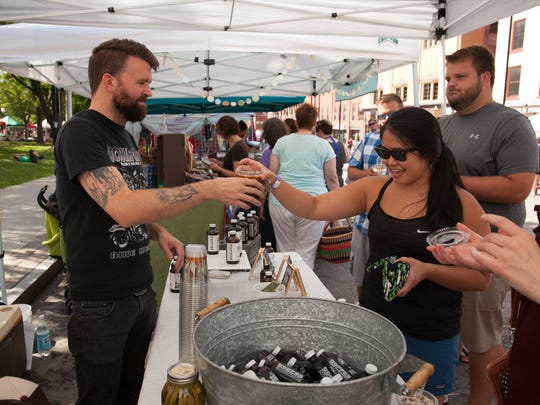 Justin Gonyea of the Northern Bayou Cold Brew Company serves up cold brew to a busy line of customers at the farmers market in Burlington on Saturday.