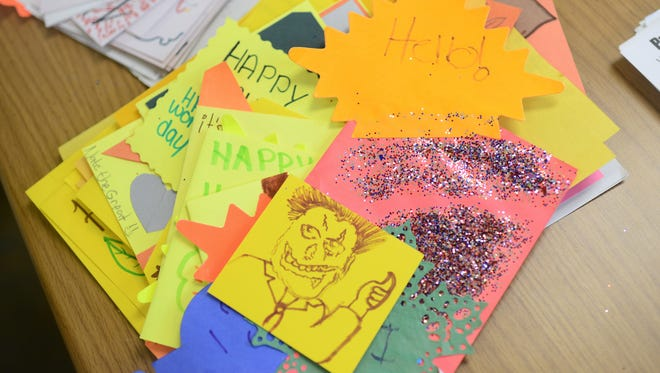 Autumn and Halloween cards made by area kids wait to be put into bags at the Volunteer Center on Wednesday. The bags will go to senior citizens who will have their yards raked by volunteers on Make a Difference Day.