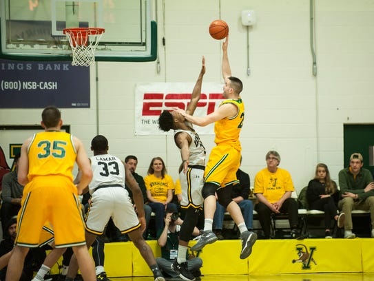 Vermont's Drew Urquhart (25) leaps to take a shot during