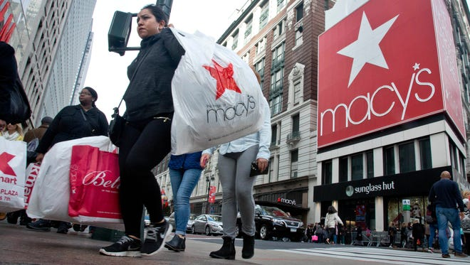 In this November 2015 file photo, shoppers carry bags as they cross a pedestrian walkway near Macy's in Herald Square in New York.  The unseasonably warm weather has left some people feeling cold about holiday shopping.  Sales of cold-weather items have been particularly icy. Sales of women's boots in New York,  are down 24 percent for the first half of December, according to Planalytics, a weather forecasting firm for retailers.  (AP Photo/Bebeto Matthews)