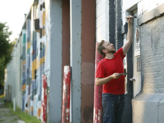 Volunteer Kevin Metz of Fairport prepares a wall with paint on Greenleaf Street in Rochester for the upcoming WALL\THERAPY.