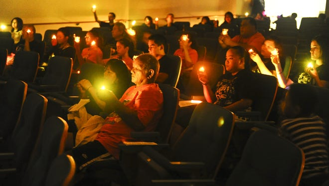 In this file photo, battery powered candles are raised by friends and family member of suicide victims during the 9th annual Out of the Darkness, Our Community Walks event.