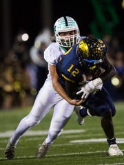 Naples High School junior, Wooby Theork, attempts to dodge a tackle from Fort Myers High School during the Class 6A regional semifinal at Naples High School on Friday, November 18, 2016 in Golden Gate.  Fort Myers High School moved on to the finals.