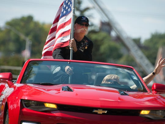 A man holds a flag during the parade in downtown Beaver