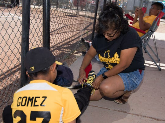 Eric Gomez gets his shoelaces adjusted by his mother
