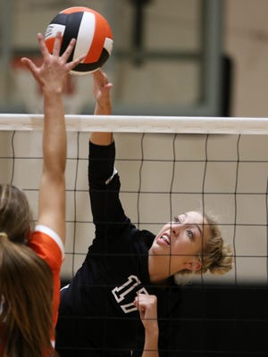 Aztec's Reagan Weaver makes a kill against Los Lunas' Mica Jenrette on Tuesday at the Lillywhite Gym. Aztec lost in straight sets.