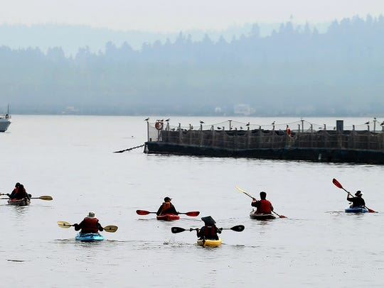 Kayakers paddle out to the fish pens in Rich Passage