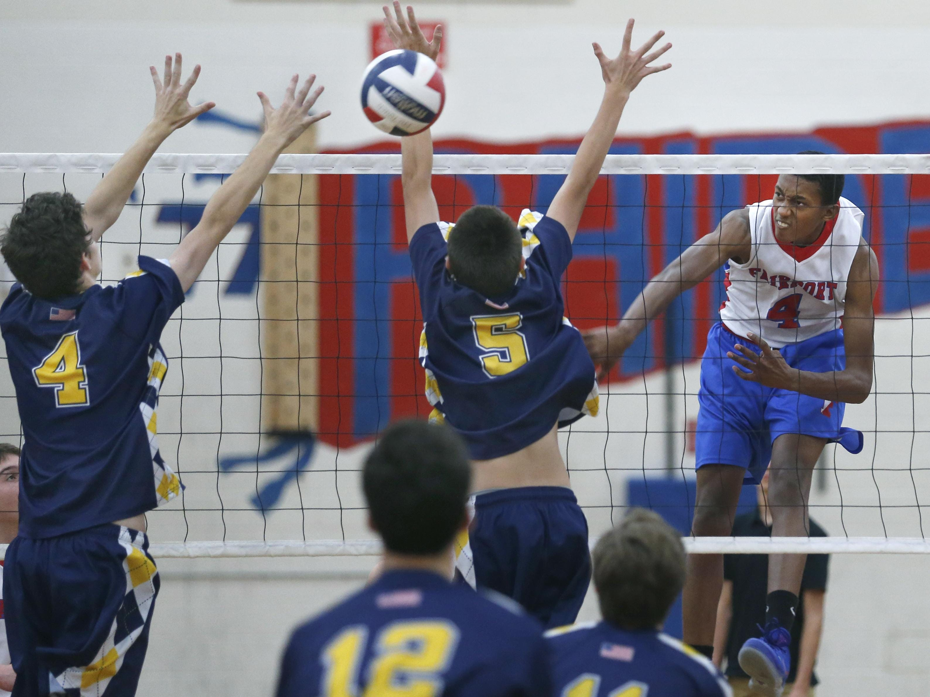 Fairport's Donovan Dey attacks against Victor's Hayden Hall and Cam Clark in the second set at Fairport High School. Fairport won in three sets.