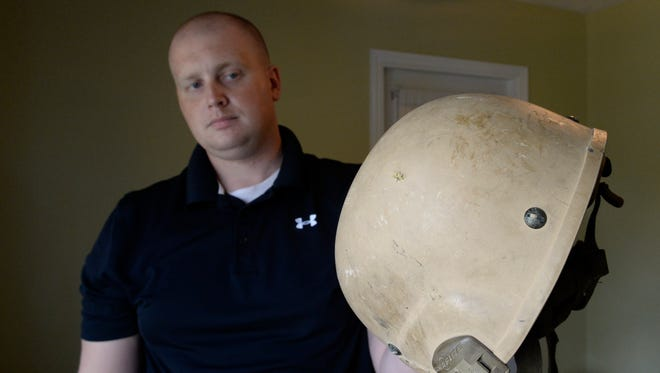Marine Staff Sgt. Michael Compton shows where a bullet went into his helmet before going across the top of his head in 2013.  Compton has been diagnosed with PTSD.