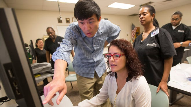 Karl Ma point to a screen while Lorena Reyna monitors a sleep patient during class at Gateway Community College in Phoenix May 26, 2015. The Polysomnography class, a sleep study/research class, originated from input from advisory groups.