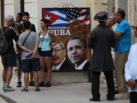 Tourists stand next to a sign showing President Barack Obama, right, and Cuba's President Raul Castro next to the Cathedral in Old Havana, Cuba on Sunday, ahead of Obama's arrival.
