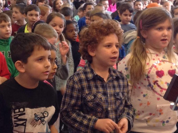Second-graders Hunter Drouillard (from left), Caleb Curto and Katelyn Morton join in singing about being readers.