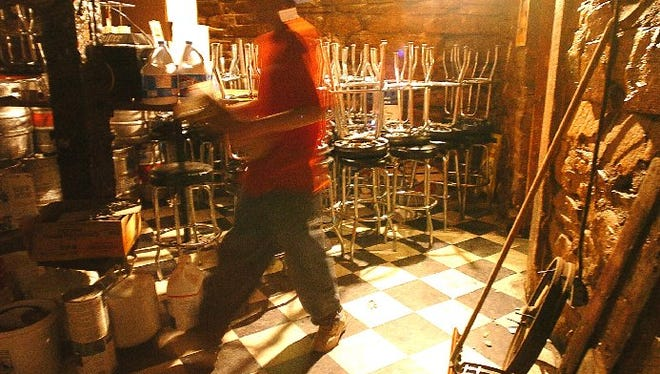 Brad Ianancone helps clean out a back room in the basement of Washington's Bar and Grill in 2004.