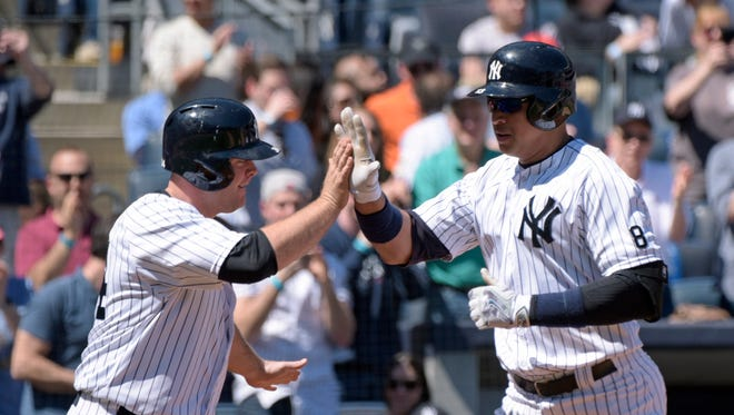 New York Yankees' Alex Rodriguez, right, celebrates with Brian McCann after hitting a two-run home run, also scoring McCann, during the second inning of a baseball game against the Seattle Mariners, Sunday, April 17, 2016, at Yankee Stadium in New York.