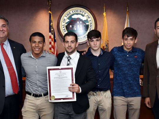 Union County Freeholder Chairman Sergio Granados and Freeholder Alexander Mirabella present a resolution to the members of the Roselle Park Wrestling Team, congratulating them on achieving 1,000 victories in its 82nd year scholastic competition, a feat accomplished by only one other team in New Jersey history.