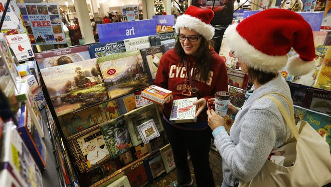 Black Friday shoppers got into the spirit of the holiday at Valley West Mall in West Des Moines, Iowa, on Friday, Nov. 27, 2015. Sarah Menzel, left, and her mother, Denise Menzel, look through calendars at a mall kiosk retailer.